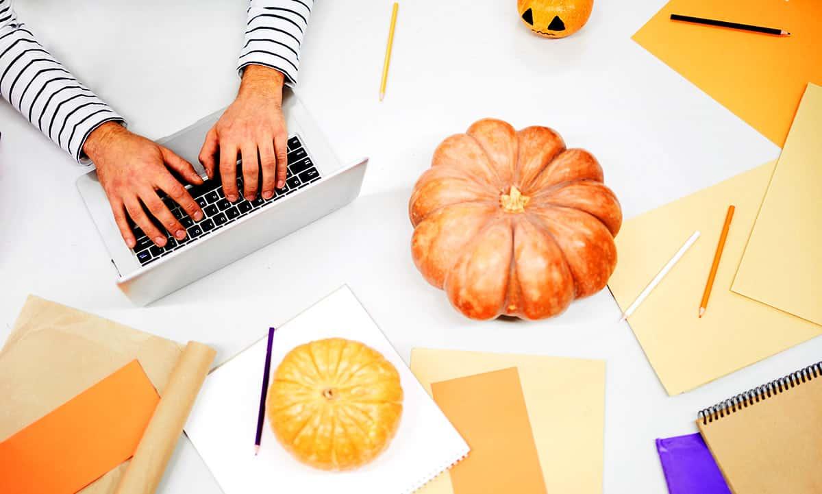 Visão de alto ângulo de um homem irreconhecível digitando no laptop enquanto encontra ideias para o Halloween e está sentado à mesa cheia de papéis laranja e abóboras