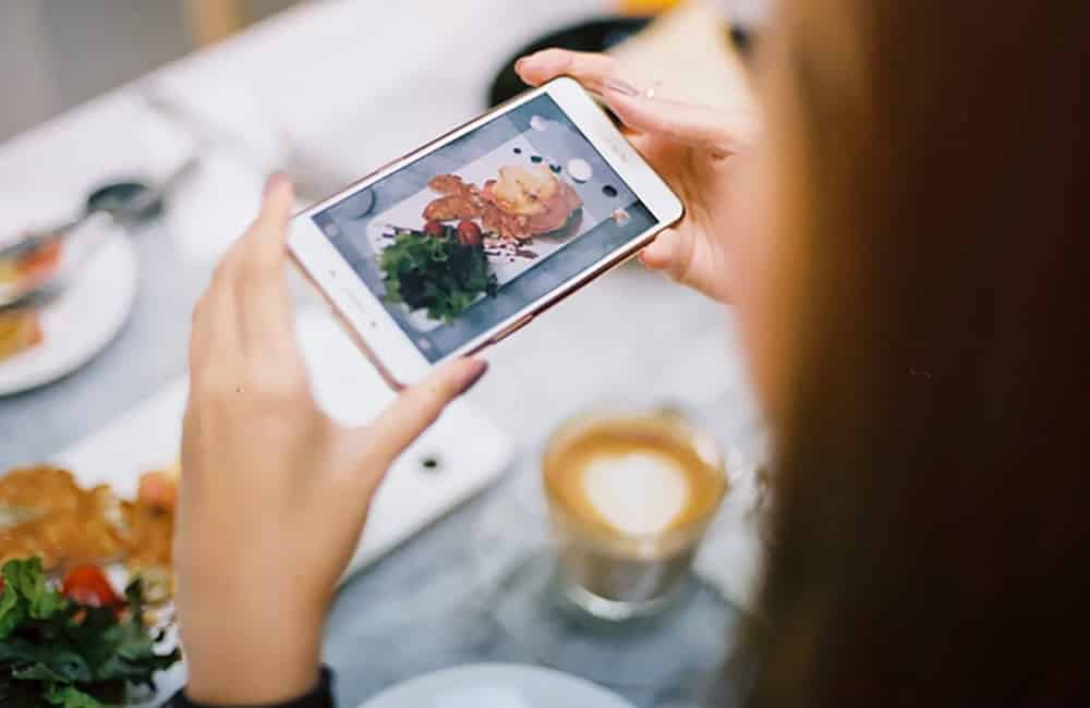 mulher a tirar foto da refeição com o telemóvel